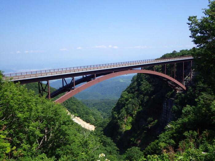 磐梯吾妻スカイラインでぜひ見てほしいスポットが、北側の高湯温泉入口にほど近い「つばくろ谷」です。本線からほんの少し脇道に入ります。つばくろ谷にかかるアーチ型の赤い橋は「不動沢橋」。はるか眼下に福島市街が見え、思わず息をのむようなビュースポットです。