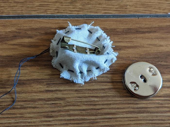 ⑧ 下のパーツよりも5~7㎜ほど大きめに、生地を丸く切り取ります。上のパーツと同様に、生地の縁より少し内側をステッチ。ぐるっと1周したら、糸を休ませたままブローチピンを縫い付けます。