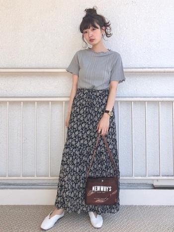 花柄のロングスカートに、グレーのメロウレーストップスを合わせたコーディネートです。フェミニンなアイテムも、クリア素材のブラウンショルダーバッグでカジュアルダウンし、大人の遊び心をプラスしています。