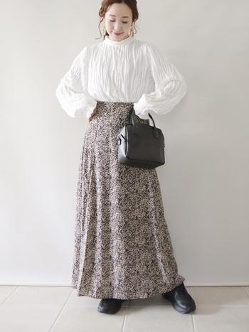 プリーツデザインのパフスリーブと小花柄のスカートでフェミニンな印象。可憐でいて甘すぎないスタイリングのポイントは足元のスニーカー。バッグとスニーカーを黒でリンクさせて、引き締め効果バツグン。