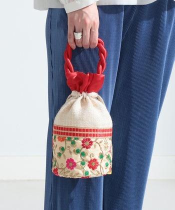 小さめなのに抜群の存在感がある、刺繍入りの巾着バッグ。360度どこから見ても、赤やオレンジ、ピンクの花が映えるデザインなので、服装をシンプルにまとめてバッグをコーデの主役にすると、おしゃれに決まります!