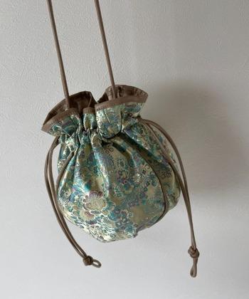 チャイナ刺繍が全体にあしらわれた巾着バッグは、シンプルコーデのワンポイントにおすすめ!ころんとしたフォルムが、なんとも可愛らしいデザインです。ブラウンのレザーパイピングが、全体の印象をきゅっと引き締めていますね。