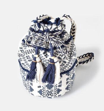 大胆な刺繍にポンポンのついたリボン、大きめのタッセルなど、コーデの主役になりそうな巾着バッグ。ひとつひとつの要素は派手ですが、ツートンカラーにすることで大人っぽい表情となり、さまざまなコーデにマッチします。筒型のデザインなので、収納力もバッチリですよ。