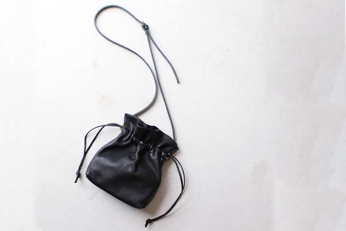 口をキュッとすぼめて閉める巾着型のバッグ。ファスナーや留め具がないおかげで、カチッと容量が決まっておらず、許容量が柔軟なのが嬉しい。筆者も愛用していますが、巾着型&レザー素材は、とにかく使い勝手が良いのです。程よく緩さもあるので、きれいめにもカジュアルにもきちんとフィットしてくれる優れもの。革が適度に肉厚だと、ドレープがしっかり出て、とても表情豊かです。