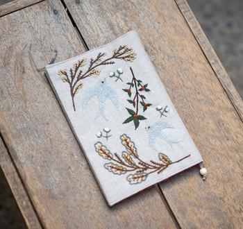 うっとりするような美しい鳥の刺繍が入ったリネン素材のブックカバーです。  すいすいと飛び回る小鳥と種類の異なる葉っぱが刺繍されています。さらりとしたリネンに丁寧に施された刺繍に触れるたび、優しい気持ちになれますよ。