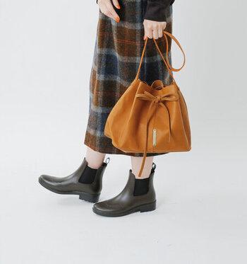 やわらかなレザーの質感と丸みのあるフォルムが印象的なこちらのバッグ。紐をキュッと絞ってリボンのように結べば、大人の可愛らしさをまとった巾着バッグとして使えますよ。ショルダーはバッグ本体に直接縫いつけられており、余計な装飾も一切ありません。そのシンプルさが、レザーの美しさをより一層引き立てています。