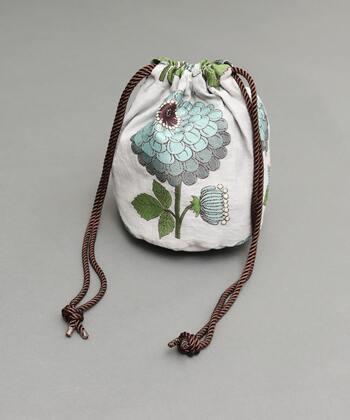どこか懐かしさを感じる大柄のダリアをあしらったデザインの巾着バッグは、持っているだけで特別な気持ちになれそう!花びらのひとつひとつが繊細なカラーで表現されており、立体感のある仕上がりになっています。大人の「かわいい」を取り入れたい方におすすめのアイテムです。