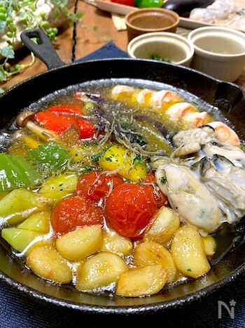 牡蠣、エビ、野菜などが入ったアヒージョ鍋。豪華なお料理なのにとても簡単です。丸ごとにんにくとスパイスの香りがたまらなくよく合います。旨味が混ざったオリーブオイルでしめのパスタは絶品です。家族やホームパーティ、キャンプでも楽しめそう!