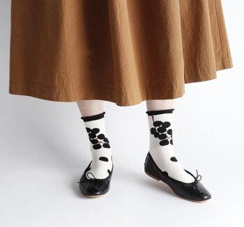 足首をきゅっと包み込んでくれる、履き口の切替デザインがお洒落な靴下。白地に花の模様が入っているのでポイントづくりにも嬉しい1足です。黒のバレエシューズと合わせてさりげなく華やかな足元に。
