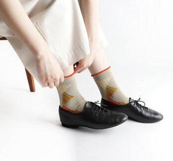 テーブルクロスをイメージしてデザインされた、三角形を用いた柄の靴下です。スーピマ綿を素材に使用しているので、滑らかな肌触りが特徴。履き口にはピコットを施し、キュートなアクセントをプラスしています。カラーはライトグリーン・オフホワイト・ブラックの3色展開です。