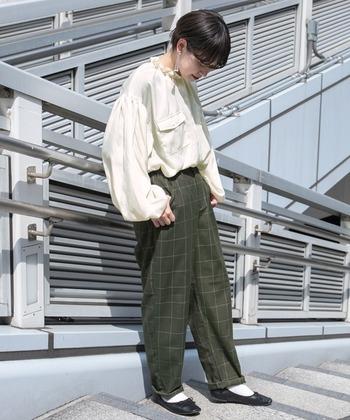 フリル付きのサテンブラウスは、メンズライクなチェックパンツと合わせてクラシカルさを残した可愛らしいコーデに。トレンドのボリューム袖のデザインもおしゃれです。