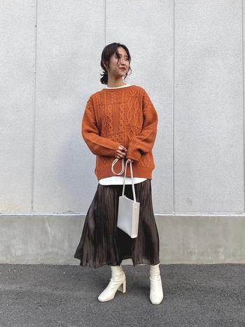 オレンジ系のニットトップスに、ブラウンのプリーツスカートを合わせたコーディネートです。白インナーをチラ見せしつつ、ショートブーツやバッグも白で統一してバランスのよい着こなしに。白小物をプラスするだけで、上品な印象がグッと高まりますね。