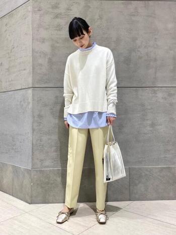 スタンドフリルのストライプブラウスを、白ニットのインナーに重ねたコーディネートです。ボトムスはセンタ―プレス入りのパンツで、オフィスカジュアルとしても使えるきちんと感抜群の着こなしにまとめています。