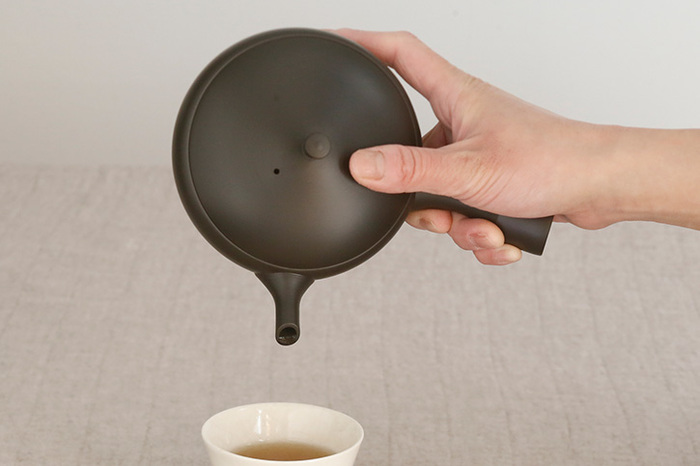 """急須というのは本来、お茶を美味しく楽しむための道具。「日本茶の味を最大限に引き出す」ことを考えて作られた""""すすむ屋"""" 茶店の急須は、茶葉が広がりやすいように、底が大きく作られているのが特徴です。また、一般の急須と比べると、高さが低く、そうすることで女性が持ちやすく、茶葉のエキスが凝縮された最後の一滴まで絞りきることが出来ます。さらに、お茶を淹れた後に残った茶殻を捨てやすいように、注ぎ口の反対に切れ込みが入っているので、お手入れもスムーズ。清潔を保ちながら使うことが出来ます。"""