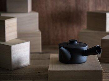 """水平、垂直のラインが際立つスタイリッシュな雰囲気の急須は、磁器作家イイホシユミコさんによるデザイン。お茶好きのイイホシさん自らが本当に使いたいと思える急須をデザインした作品なんだそうです。 """"萬古焼""""は吸水性が少ないという特徴があるため、淹れたお茶の匂いが付きにくく、味が落ちにくいのだそうです。"""