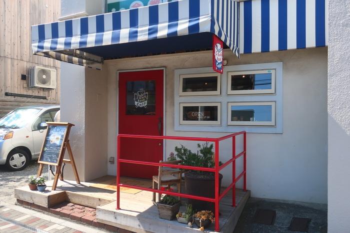 「SONG BOOK Cafe(ソングブックカフェ)」は由比ケ浜駅からすぐの場所にあります。ストライプのファサードと赤いドアの外観が目印です。