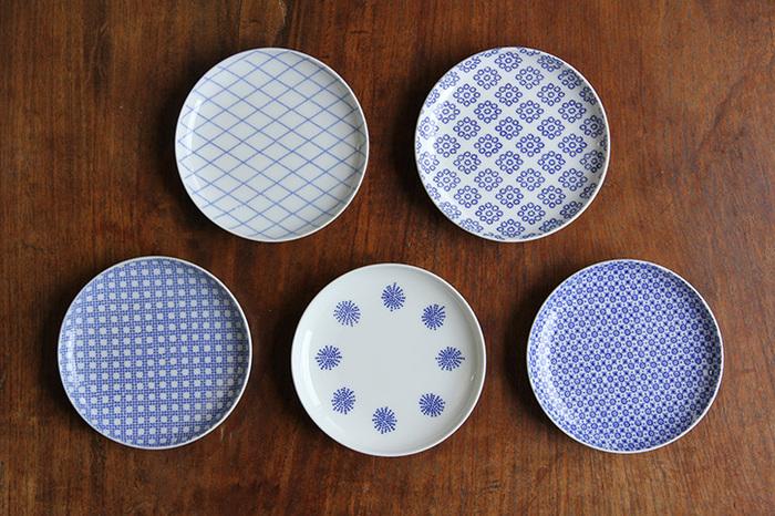 味わい深い色柄が魅力的な「東屋」の「印判小皿」。明治の頃に開発された、版を作り素地に転写する絵つけの手法である「印判」技術により制作されており、画像の左上から時計回りに「引綱」、「九曜」、「菊十」、「唐松」、「格子」の5柄があり、どれも日本の紋様をモチーフにしています。