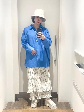 ビッグシルエットのブルーのシャツに揺れるレイヤードロングスカートを合わせ、素材感の違うテイストを楽しむコーデ。足元にはごつめのサンダルに薄手靴下をプラスし、バケットハットの白とリンクさせています。  白×ブルーの爽やかな夏らしいカジュアルコーデです。