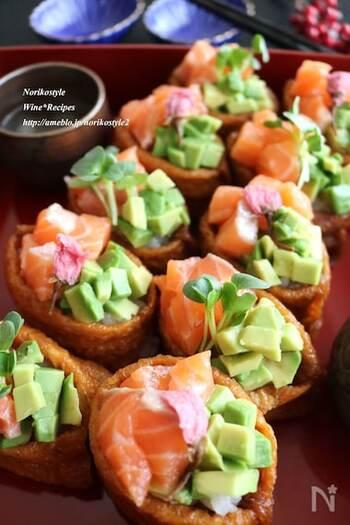 サーモンとアボカドの盛り付けが美しいアレンジいなり寿司。市販のいなりあげを使うので、酢飯を用意すればあっという間に作れます。カイワレや桜の塩漬けを添えて華やかに。
