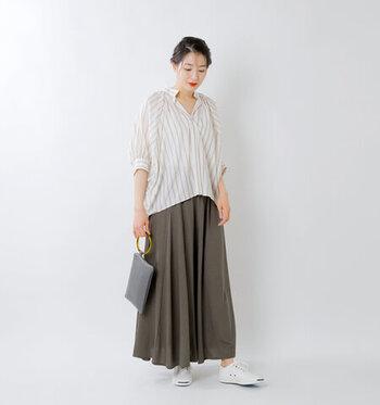 カーキグレーのフレアスカートに、ベージュのストライプシャツを合わせたコーディネートです。長めのロング丈スカートは、あえて深めのVネックトップスを選ぶことで抜け感を演出。足元は白のスニーカーをチョイスしてナチュラルな雰囲気でカジュアルさをプラスしています。