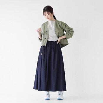 ネイビーのスカートに、白×ブルーの爽やかなスニーカーを合わせたコーディネートです。トップスは白でシンプルにまとめて、カーキのライトジャケットでクールな印象にまとめています。