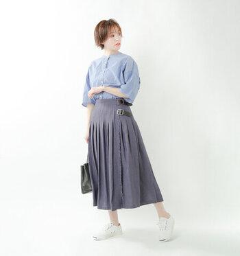 グレーのプリーツスカートに、青のシャツを合わせたコーディネート。足元は白のスニーカーで爽やかに。涼しさを感じる季節には、カーディガンなどを羽織っても上品なスタイリングに仕上がりますよ。