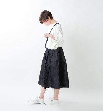 黒のスカートに、白トップスをタックインしたモノトーンコーデ。足元のスニーカーは白で、ショルダーバッグは黒と小物もモノトーンで揃えているのがポイント。シンプルながらもこなれ感のある着こなしです。