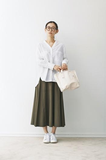 カーキカラーのフレアスカートに、白のシャツを合わせたコーディネートです。シャツと色を合わせた白スニーカーとトートバッグで、重めのカーキカラーをすっきりと着こなしています。首元と足首を見せることでスタイルアップ効果も◎