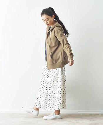 ドット柄の白スカートに、白のスニーカーを合わせたコーディネートです。ブラウンのパーカーを羽織って、キュートな印象のドット柄スカートをカジュアルに着こなしています。大人のデイリーコーデにも、ぴったりな装いですね♪