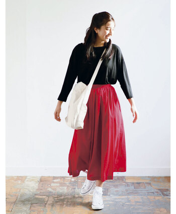 パッと目を引く赤のスカートに、黒のシンプルトップスをタックイン。色の濃いアイテム同士なので、スニーカーとバッグは白ですっきりとスタイリングしています。足し引きのバランスがとれた、シンプルながらもテクニックを感じるコーディネートです。