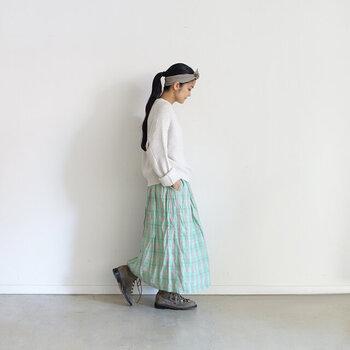 明るめグリーンのチェック柄スカートに、グレー系のスニーカーを合わせた着こなしです。白のシンプルなトップスをチョイスして、スカートが主役になるようコーディネート。頭にはスニーカーと同系色のヘアバンドをプラスして、統一感のあるスタイリングにまとめています。