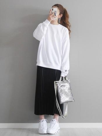 白のシンプルなスウェットに、黒のプリーツスカートを合わせたコーディネート。ごつめの白スニーカーで、繊細な印象のプリーツスカートコーデにスパイスをON。季節感のあるクリアバッグを、モノトーンコーデのアクセントに活用しています。