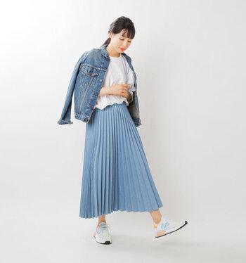 ブルーのプリーツスカートに、白トップスをタックインしたコーディネート。足元は白ベースにブルーのラインも入ったカラフルなスニーカーで、上品なプリーツスカートをアクティブスタイルにアップデートしています。デニムジャケットも明るめのブルーを合わせて統一感ばっちりです。