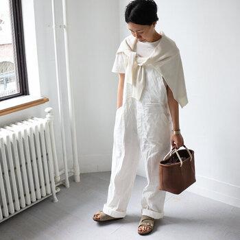 白のオーバーオールに、白Tシャツとカーディガンを合わせたワントーンコーデ。トートバッグとサンダルでブラウン系のカラーを取り入れて、ホワイトコーデのアクセントに活用しています。オーバーオールの裾をラフにロールアップして、サンダルをしっかり覗かせることで季節感のアピールにも◎