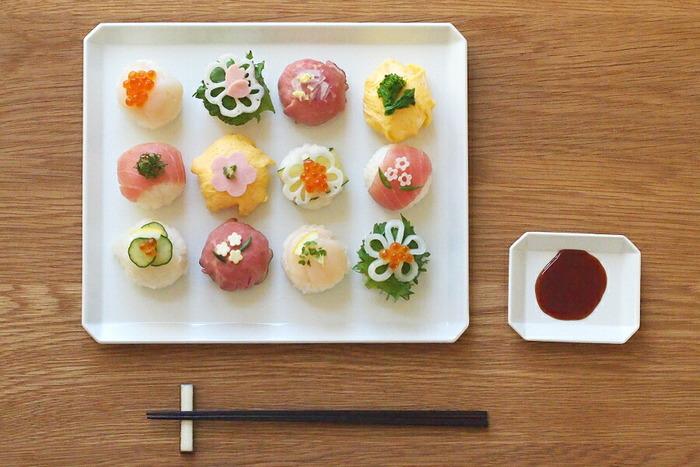 長角皿に色とりどりのお寿司を並べるだけで存在感のあるおもてなし料理になります。具材を上にあしらって豪華なイメージに。お花をモチーフにした飾りは季節感がでて、和やかになりますね。整列させた盛り付けの場合、シソの葉の緑色やいくらの赤色など色彩でアクセントをつけると洗練されます。大人数で集まるパーティにおすすめです。