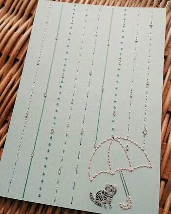 罫線を雨で表現するアイデアが素敵です。傘と猫ちゃんがこちらをじっと見つめていて、ストーリー性を感じるデザインもいいですね。