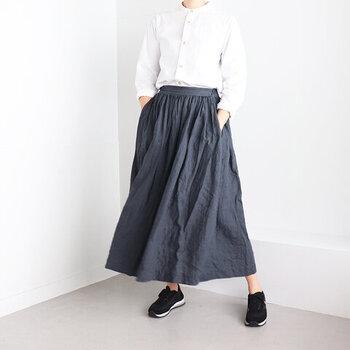 黒のリネン素材スカートに、黒のスニーカーを合わせたキレイめなモノトーンコーデ。ソール部分が白のスニーカーは、白シャツとの相性も抜群。トップスはスカートにタックインしてすっきりと着こなして。