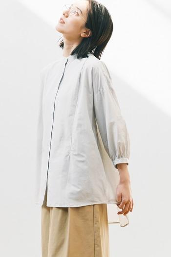 すっきりシルエットにふわっと控えめに膨らんだ袖。襟元はバンドカラーで慎ましく。コットンシルクの布の落ち感がきれいなシャツは、清楚な佇まい。シンプルだけど、エアリーな表情がとても素敵です。
