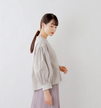 肩の落ち感から自然な流れでふんわり膨むボリュームスリーブが印象的なブラウス。裾はヘムラインでボトムとのバランスを取りやすいデザイン。程よいハリと光沢があるコットンツイル地が華やかで、よそ行きスタイルにも似合います。