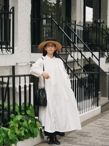 ふんわりシルエットの白いシャツワンピース。1枚で着ても素敵だけど、黒のボトムやバッグでピリッと引き締めるのもいい。黒いリボンの麦わら帽もアクセントになっています。