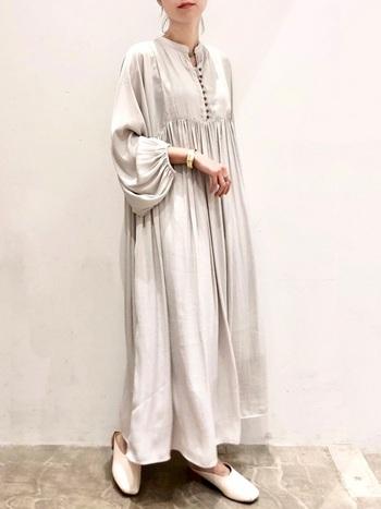 布の有機的な流れが女神のような空気感を醸し出す優美なワンピース。ボリュームスリーブから覗く手首にバングルというさりげない合わせ技も真似したくなります。