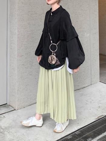 綺麗なライトグリーンのプリーツスカート。ボリューム袖のチャイナブラウスが印象的ですが、黒なのできちんと上半身を引き締めてスカートのグリーンも引き立たせていますね。ブラウスの裾からチラリと見える白インナーが実は上下のバランス役。甘めコーデはスニーカーでほどよくカジュアルダウンを。