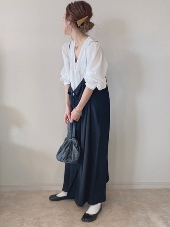 Aラインシルエットがエレガントな黒のキャミソールワンピースは、前後2通りのデザインを楽しめます。白ソックス+黒バレエシューズ、巾着バッグ、ふんわりお袖のブラウスなど、女性らしいアイテムでまとめてフェミニンに仕上げましょう。