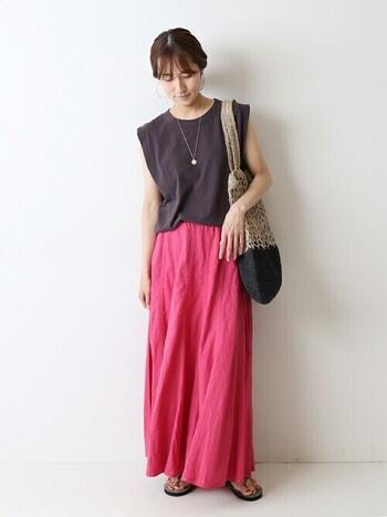 まさにピンクのスカートを主役にしたコーデ。このようにダークグレーや黒などの色の濃いトップスと合わせることで、ピンクの鮮やかさを更に引き立てることができます。夏仕様で肌を見せているのも、ベージュのバッグとの統一感が出て◎