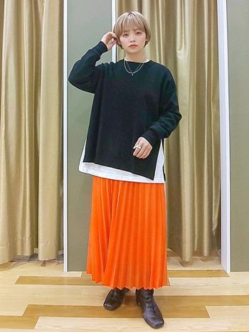 パキッとした色味のオレンジでも、透け感のある素材であればたちまち柔らかな印象に。歩くたびにふわりと揺れる綺麗なプリーツスカートと、深いスリットが入った黒のニット。インナーの白がそれぞれの色をくっきりと美しく見せてくれています。