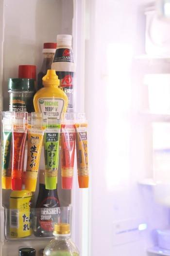 ダイソーの薬味チューブフックを使って、冷蔵庫ポケットにたくさんの薬味を引っかけ収納。フックが透明なので賞味期限の表示を隠さないのがポイントです。