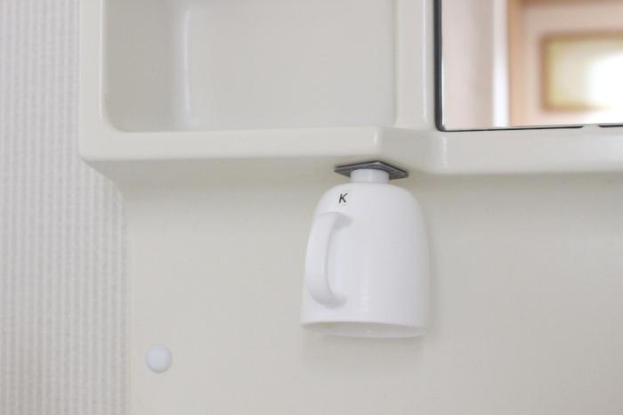 洗面台にマグネットを使ってコップを逆さまに収納するアイデア。水が溜まらないのでぬめり知らずで、衛生的ですね。洗面台の棚裏にマグネットを付けるので目立たないのもポイント。