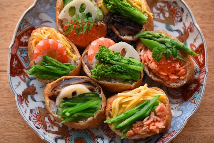 いなり寿司のおあげの上を閉じずに、お好みの具を乗せる「オープンいなり」は、味も彩りもバラエティがあって、おもてなしやホームパーティにぴったり。赤と茶、黄色、緑をバランスよく乗せて華やかに。
