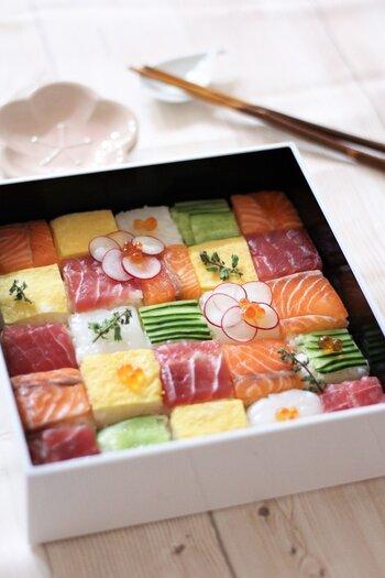 華やかなお祝いやおもてなしの席にぴったりなのが「押し寿司」。牛乳パックや保存容器など、身近にあるもので作れます。まぐろやサーモンの赤、きゅうりの緑、卵の黄色にイカの白、お花畑みたいな押し寿司です。