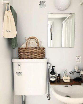 トイレタンクの上にかごを置いて収納に。巾着に入れることで中身が見えないのも気遣いを感じます。洗面周りのアイテムは、茶色と白でまとめることですっきり。洗面ボウルに直接置くのではなく、木の板を使ってスペース確保&おしゃれに見せているのはぜひ真似したいアイデアです。